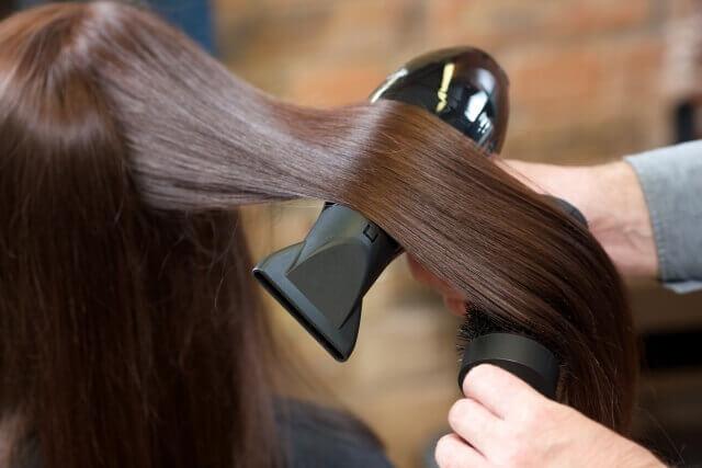 髪をブローする美容師の写真