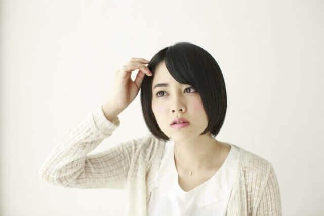 髪の毛を気にする女性の写真
