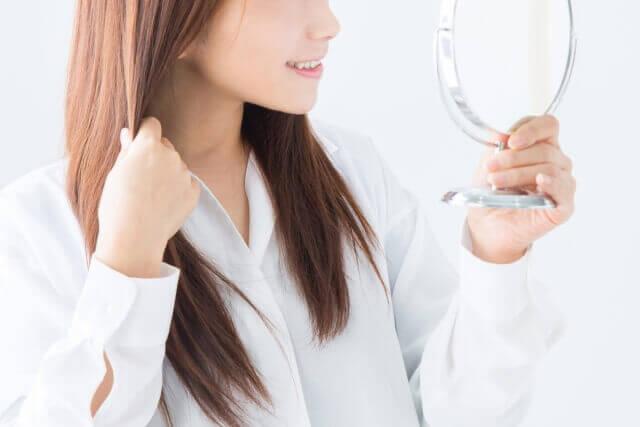 髪をチェックする女性の写真