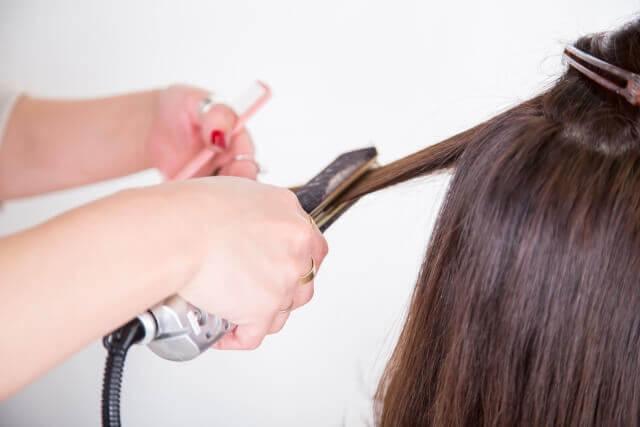 ストレートアイロンで髪を伸ばす写真