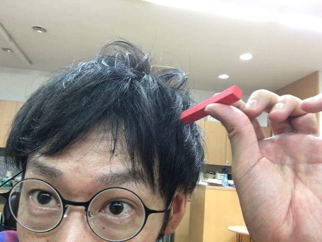 赤色のカラーチョークを髪の毛に付けている写真