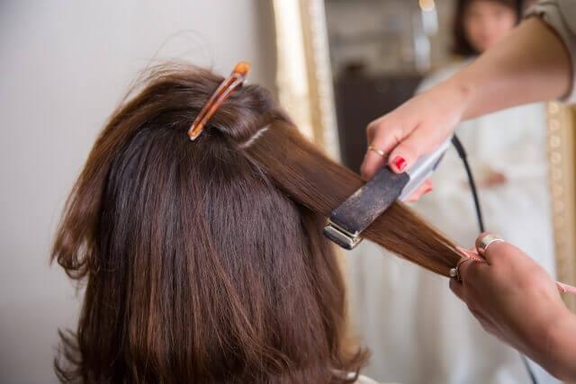 ストレートアイロンで髪を伸ばしている写真