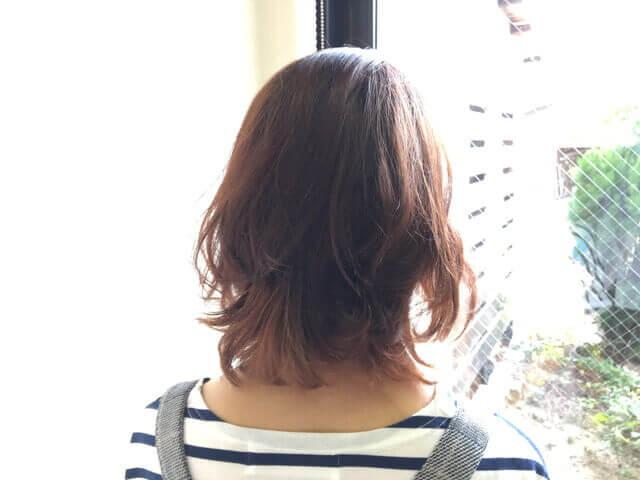 光りに透かせたブリーチありの髪の毛をグレーアッシュで染めた写真