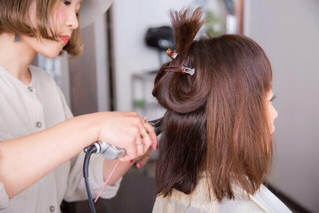 ストレートアイロンを使う美容師の写真