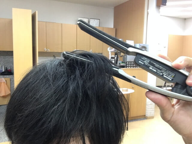ストレートアイロンで髪の毛をはさむところの写真