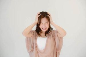 頭をかかえる女性の写真