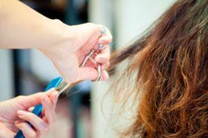パーマヘアを切る美容師