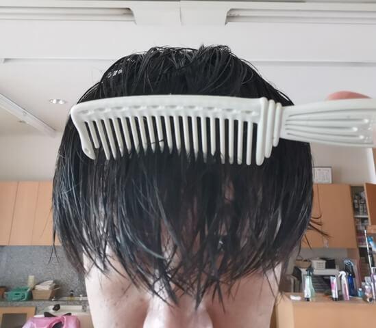 洗い流さないトリートメントをつけてとかしている髪