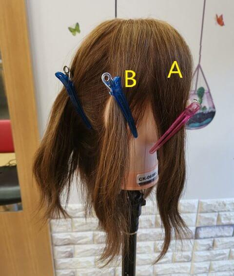 ウェーブヘアにする髪を分けた写真