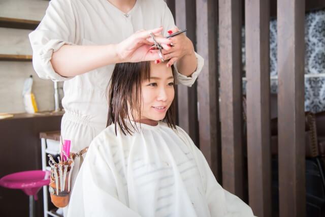 前髪を切る女性