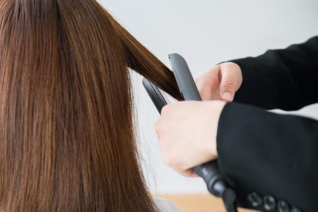 ヘアアイロンで髪を伸ばす美容師