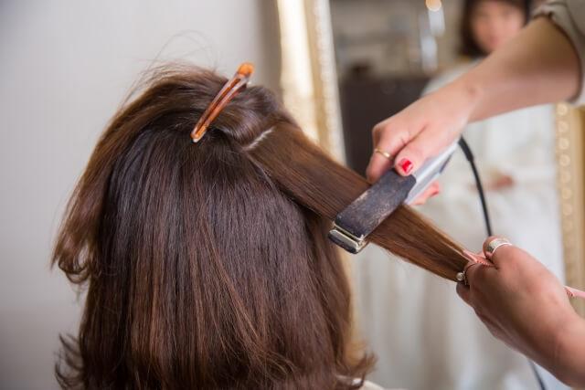 ストレートアイロンで髪を伸ばされる女性