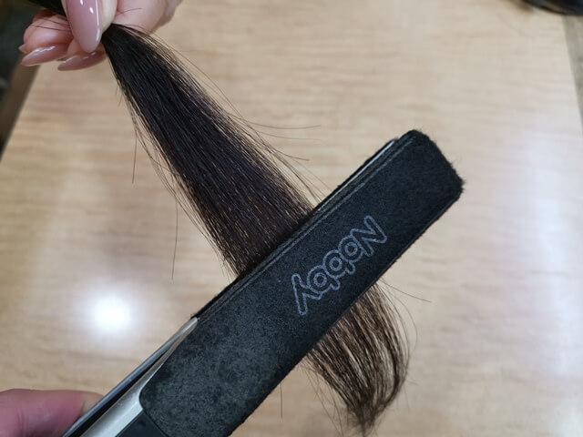 ストレートアイロンで伸ばしている髪