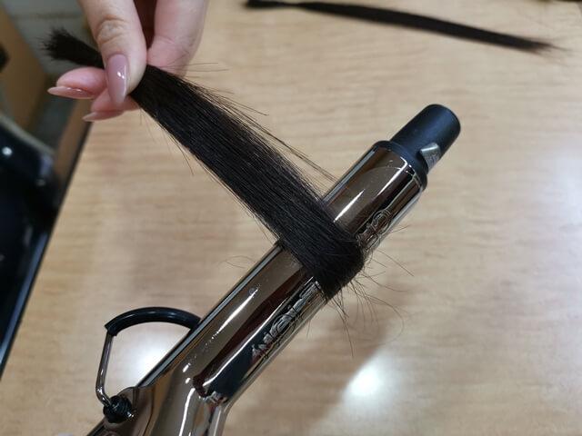 毛先をコテで巻いている髪