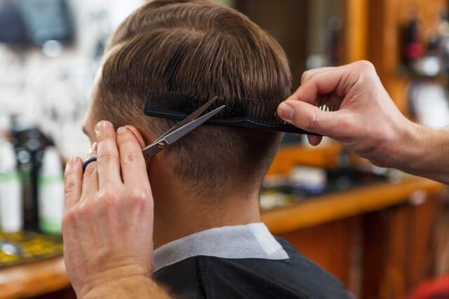 髪を切られる男性