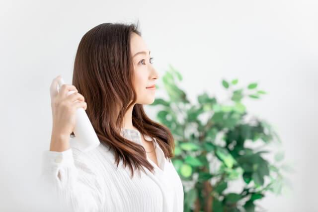 髪にスプレーをかける女性