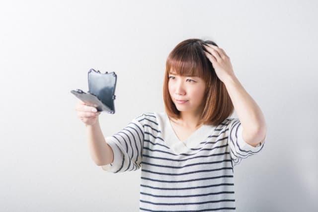 髪の毛に悩む女性